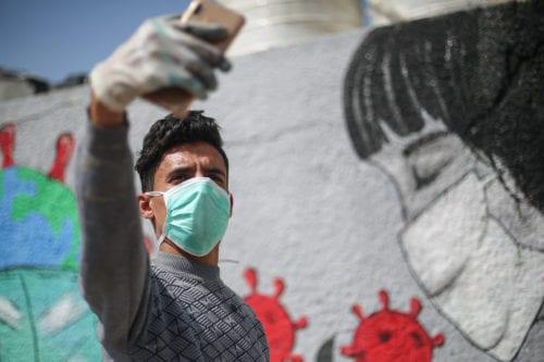 Palestinian painters draw graffitis to draw attention to the coronavirus (COVID-19) pandemic in Khan Yunis, Gaza on 28 March 2020 [Mustafa Hassona/Anadolu Agency]