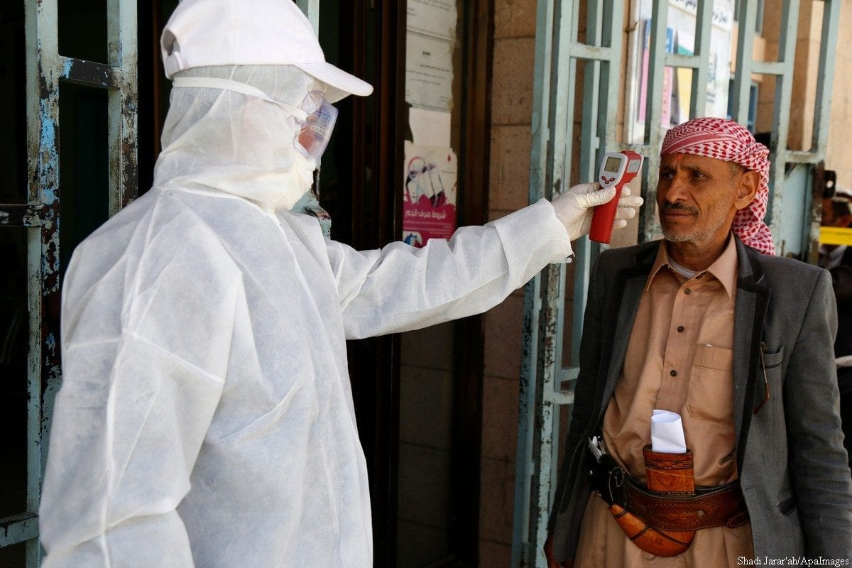A medical worker measures body temperature of a man at a state-run facility as a precautionary measure to combat COVID-19 on 24 March 2020 in Sana'a, Yemen [Mohammed Hamoud/Getty Images]