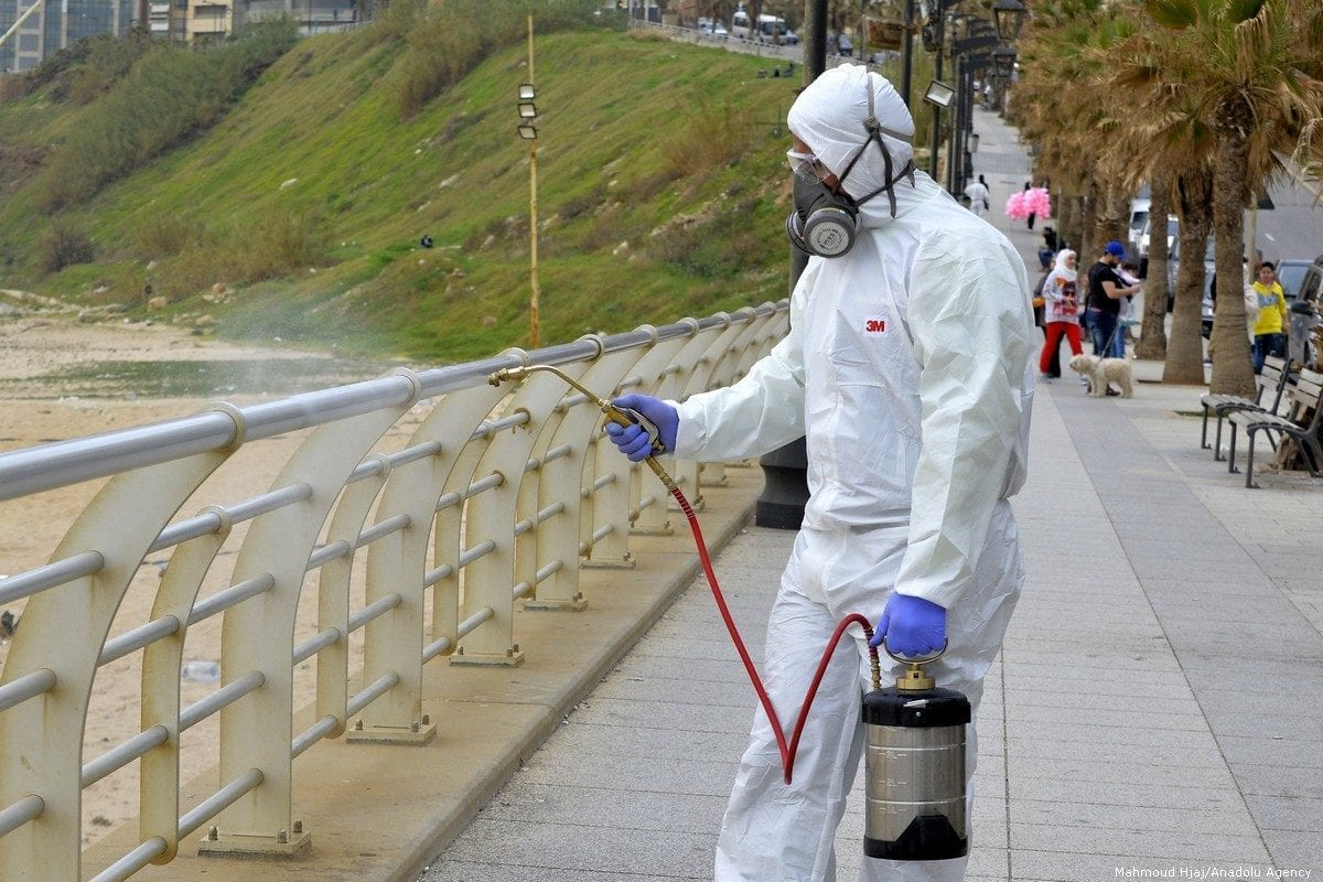 A health official wearing protective suit sprays disinfectant as a precaution against the coronavirus in Beirut, Lebanon on 5 March 2020 [Hussam Chbaro/Anadolu Agency]