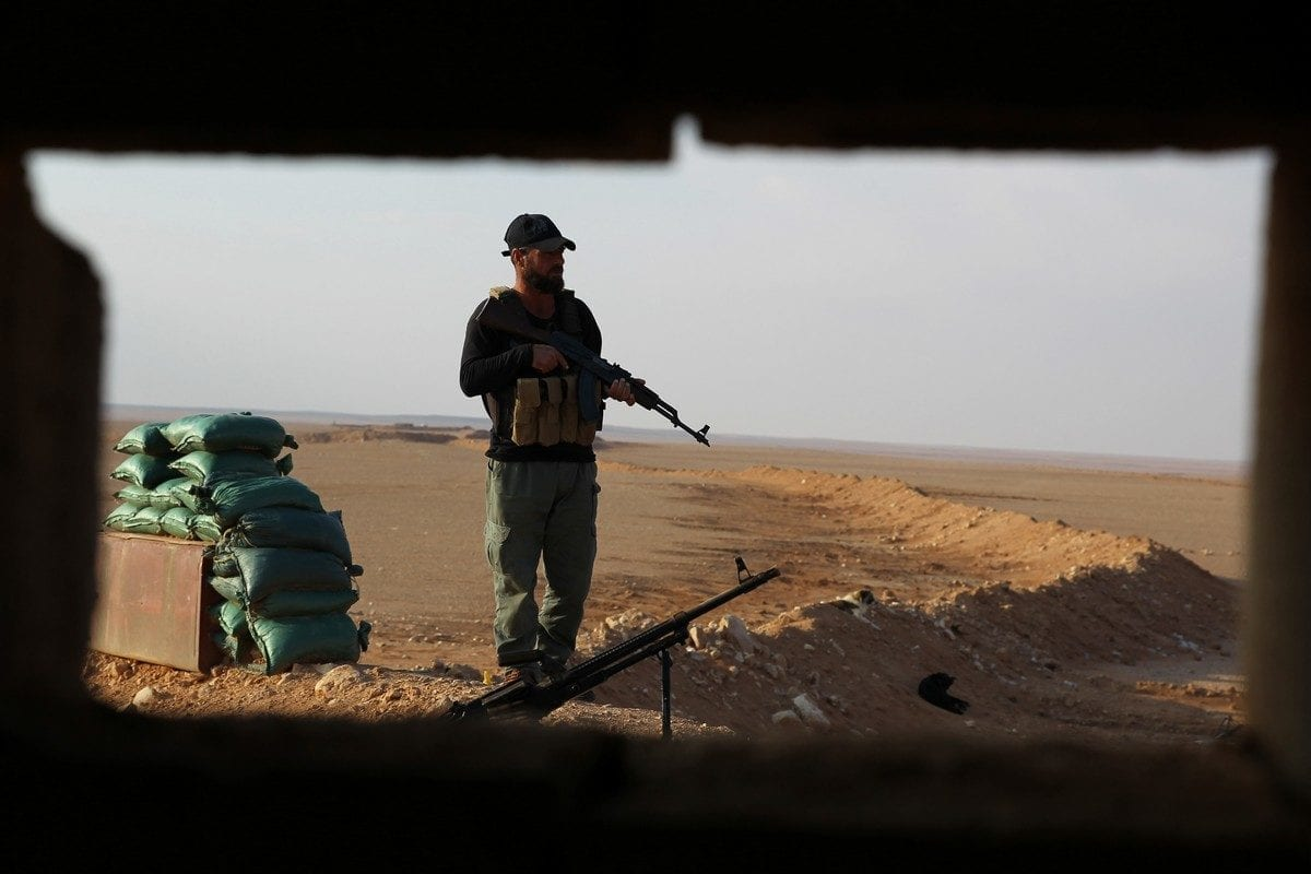 A Shiite fighter stands guard at a border position near Syria's Deir Ezzor region on 12 November 2018 [AHMAD AL-ARUBAYE/AFP/Images]