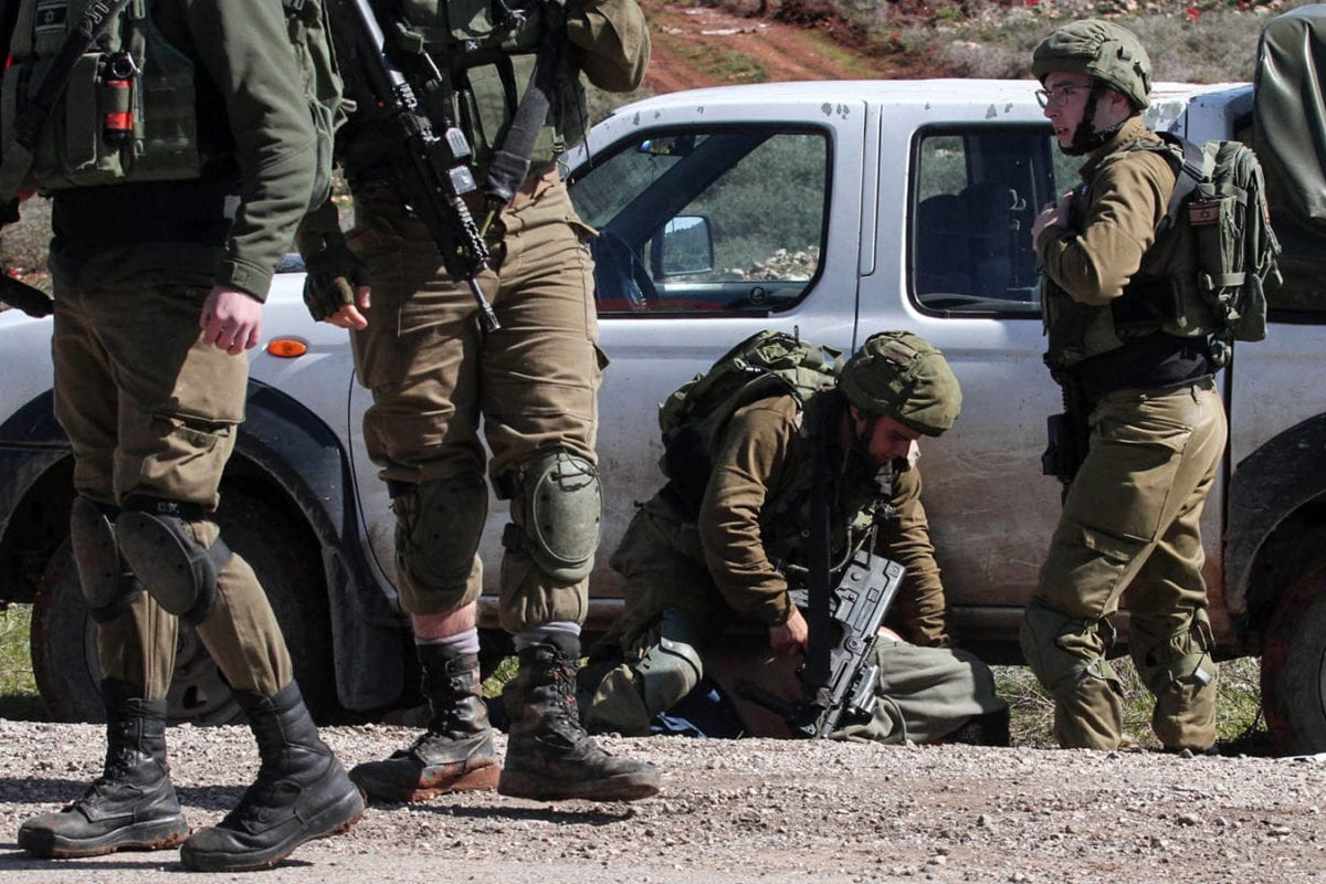 Israeli soldiers arrest a Palestinian protester during protest against bulldozing operations carried out by the occupation bulldozers near the village of Aqraba, south of the West Bank city of Nablus on 3 March2020. [Ayman Nobani/ WAFA]