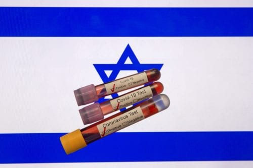 In this photo illustration coronavirus (COVID-19) positive blood samples are seen in front of a computer screen displaying the flag of Israel on 6 April 2020 in Izmir, Turkey. [Mehmet Emin Mengüarslan - Anadolu Agency]