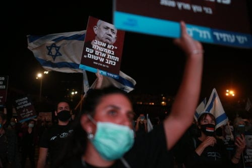 Israelis, wearing protective face masks gather to protest against Prime Minister Benjamin Netanyahu at Rabin Square in Tel Aviv on 19 April 2020 [Daniel Bar On/Anadolu Agency]