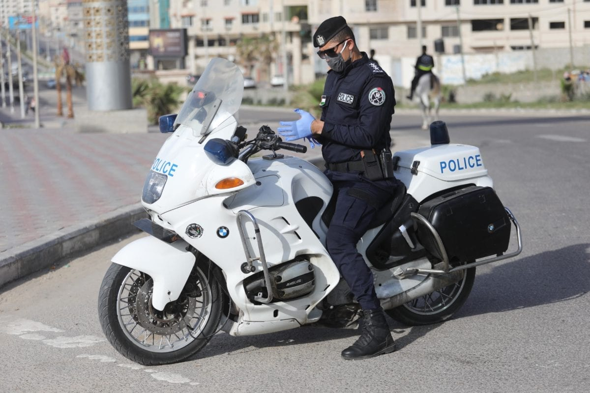 Gaza police stop cars parking along the beach to reduce public gatherings in an attempt to tackle the coronavirus in Gaza on 11 April 2020 [Mohammed Asad/Middle East Monitor]