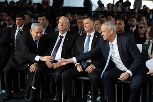 Israeli Blue and White party chief Benny Gantz (R), shakes hands with Prime Minister Benjamin Netanyahu (L) as they attend a state memorial ceremony for former Israeli prime minister Yitzhak Rabin (backround) and his wife Leah, at Mount Herzl in Jerusalem on 10 November, 2019 [HEIDI LEVINE/POOL/AFP via Getty Images]