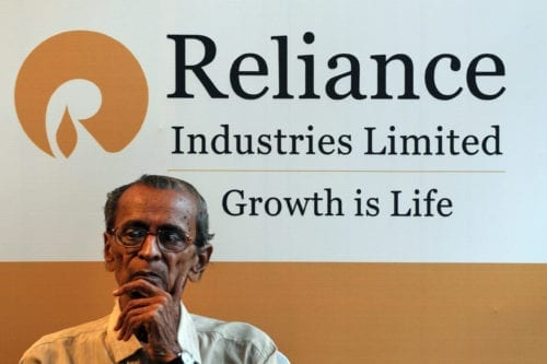 A shareholder sits beside a Reliance Industries Limited poster during the company's annual general meeting in Mumbai, on June 7, 2012. [INDRANIL MUKHERJEE/AFP/Getty Images]