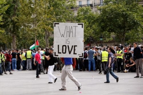 "A man carries a placard reading ""What is Love"" on the Republique square in Paris, during a banned demonstration against Israel's military operation in Gaza and in support of the Palestinian people, on 26 July, 2014 [KENZO TRIBOUILLARD/AFP via Getty Images]"