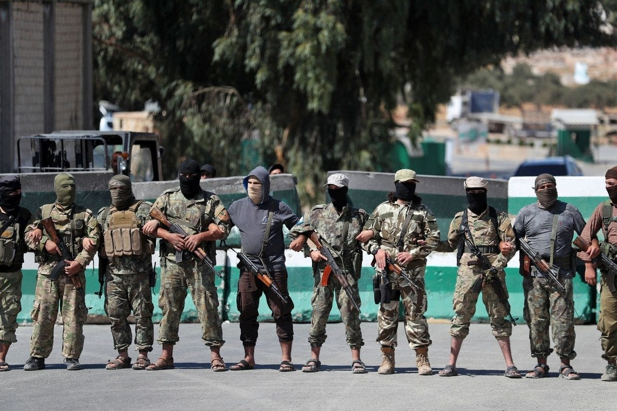 Members belonging to Hayat Tahrir Al-Sham between Turkey and Syria's northwestern Idlib province on 20 September 2019 [OMAR HAJ KADOUR/AFP/Getty Images]