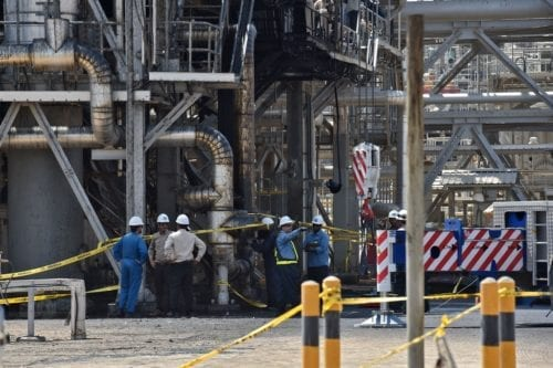 Employes of Aramco oil company stand near a heavily damaged installation after the facility was attacked on 20 September 2019 [FAYEZ NURELDINE/AFP/Getty Images]
