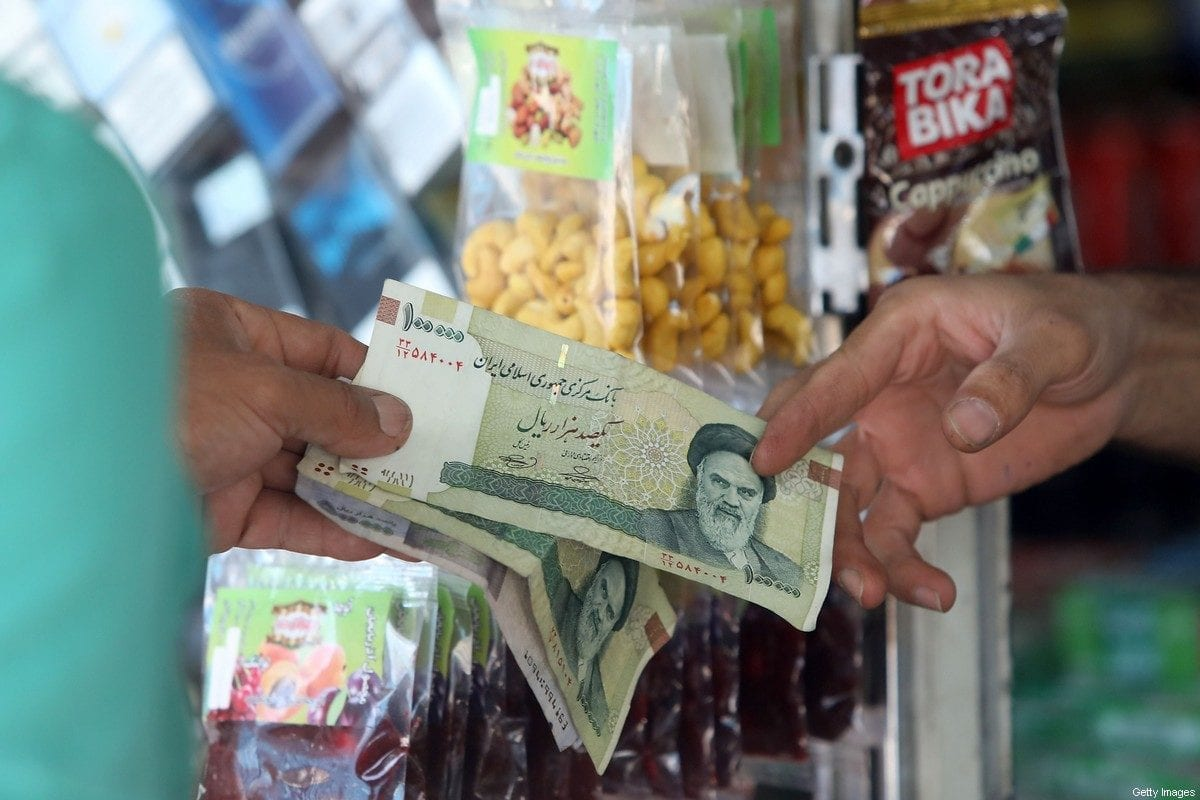 A man pays using Iranian rials at a shop, in Tehran on July 31, 2019 [ATTA KENARE/AFP via Getty Images]