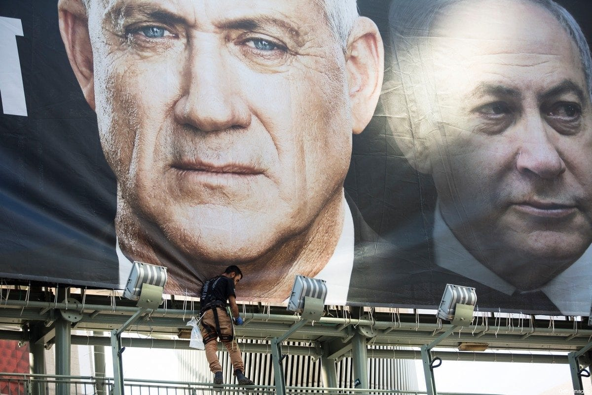 Workers hang a Blue and White Party billaboard showing its leader Benny Gantz and Israeli Prime Minister, Benjamin Netanyahu, as part of the party's campaign on 17 February 2020 in Tel Aviv, Israel. [Amir Levy/Getty Images]