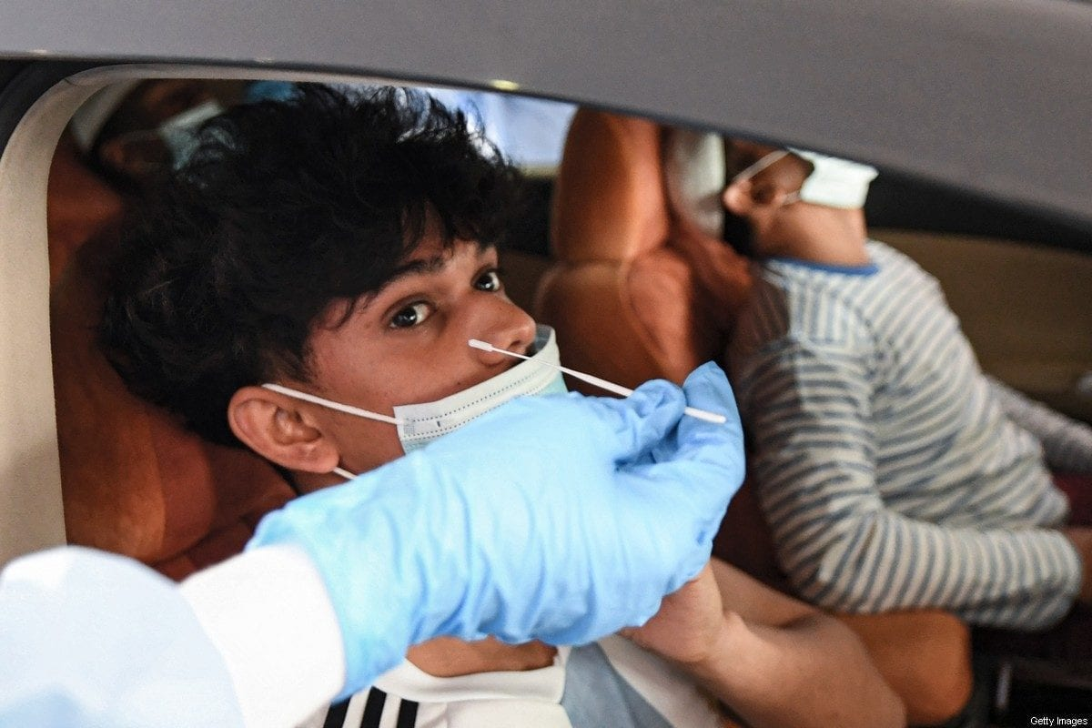 A medical staffer obtains a swab sample from a child inside a vehicle at a drive-through COVID-19 coronavirus testing centre in al-Khawaneej district of the gulf emirate of Dubai on April 9, 2020. [KARIM SAHIB/AFP via Getty Images]