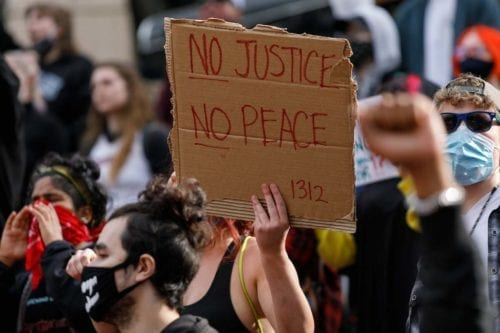 People carrying banners march to protest over the death of George Floyd an unarmed black man who died after being pinned down by a white police officer in USA on 31 May 2020 in Portland, Oregon. [John Rudoff - Anadolu Agency]