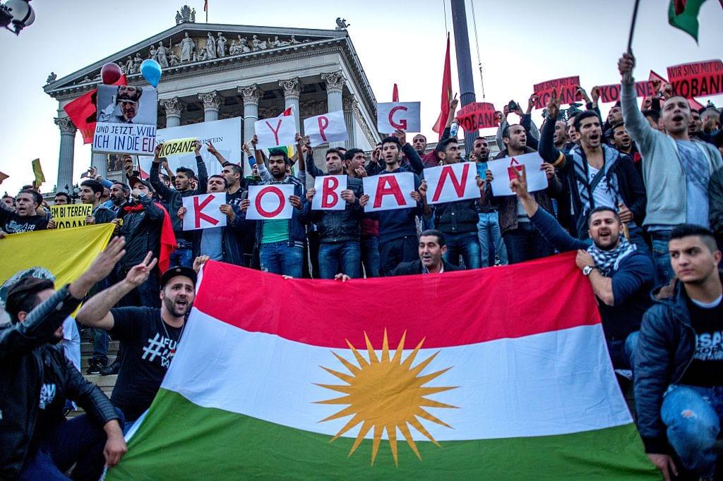 Pro Kurdish supporters wave a Kurdish flag as they march by Austrian Parliament [JOE KLAMAR/AFP via Getty Images]