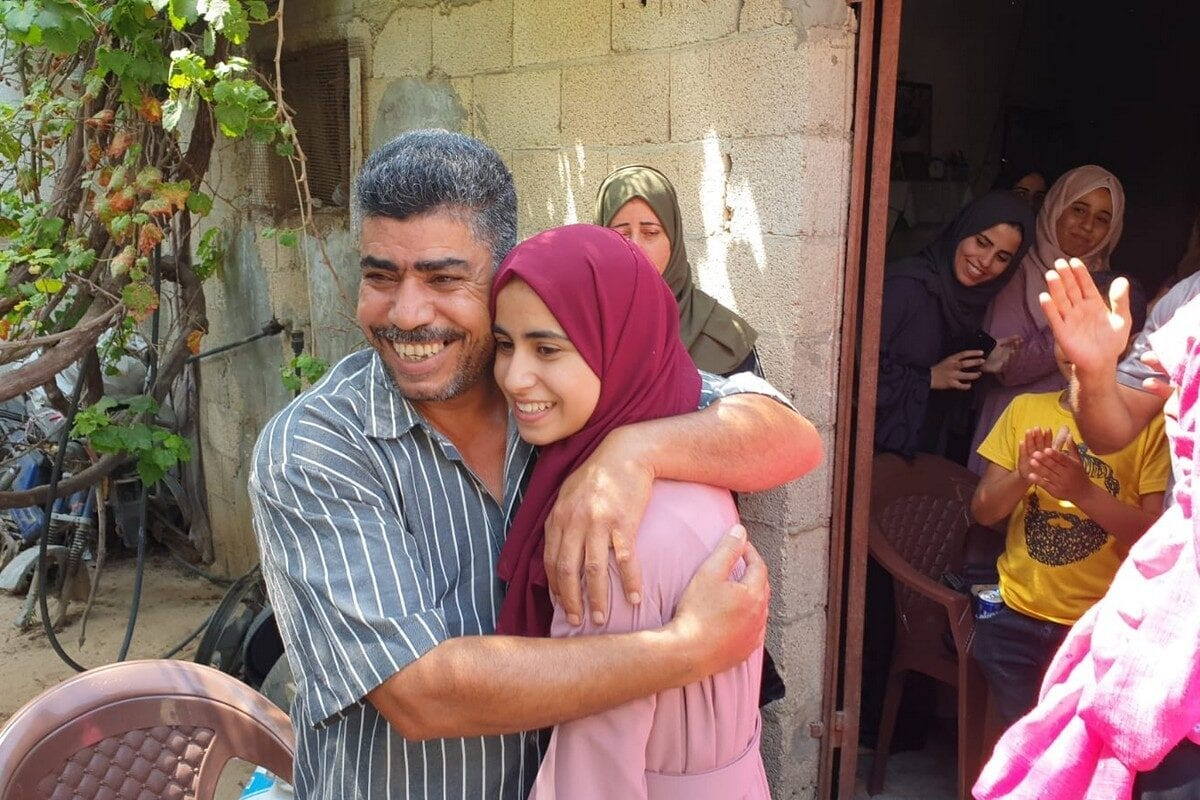 Shams Abuamra with her father after she enjoyed great success in her Tawjehi exams , Khan Younis, 11 July 2020 [Hasan Eslayeh]