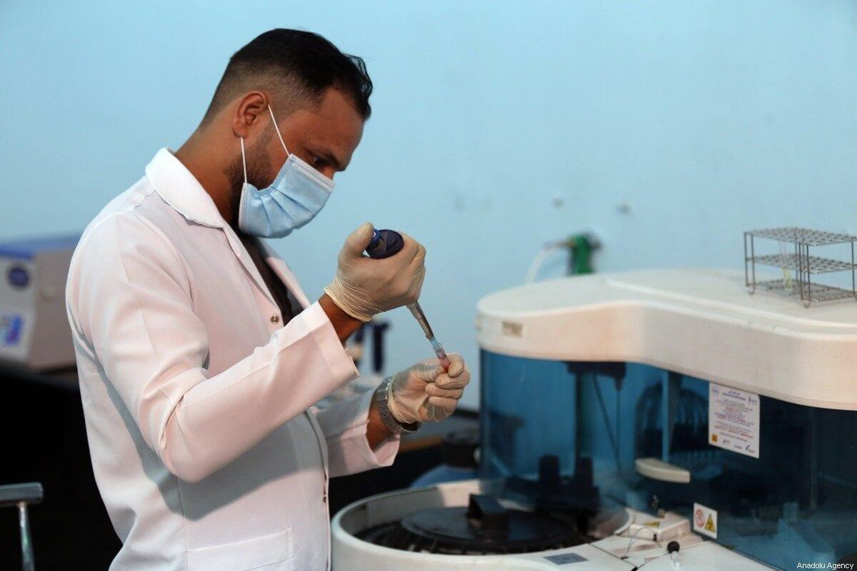 A health official works on a sample in International Fair ground in Baghdad, Iraq on 18 July, 2020 [Murtadha Al-Sudani/Anadolu Agency]