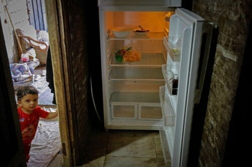 A Lebanese child stands next to an empty refrigerator in Beirut as Lebanon suffers economic crisis plunging many into poverty, 17 June 2020 [IBRAHIM CHALHOUB/AFP/Getty Images]