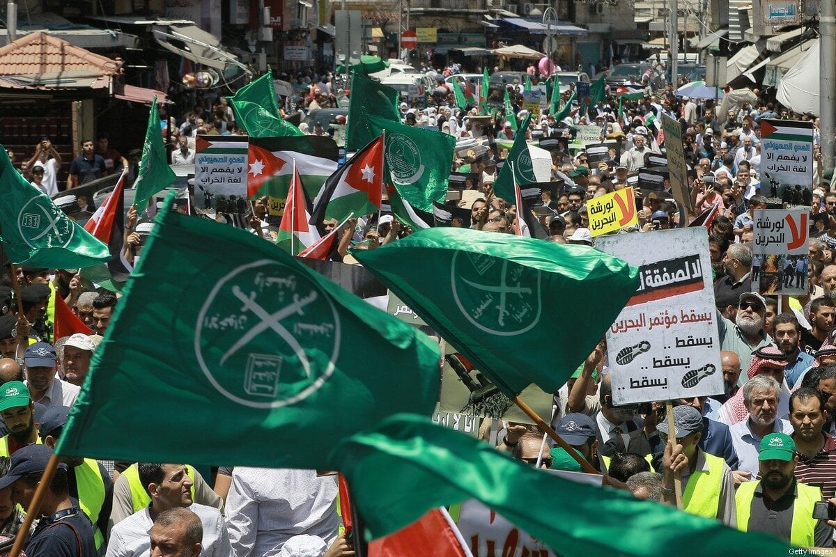 """Flags of the Muslim Brotherhood, Jordan, and other political parties are waved with other protest signs denouncing the US-led Middle East economic conference in Bahrain, during a post-Friday prayers demonstration against US President Donald Trump's """"Deal of the Century"""" in the Jordanian capital Amman on June 21, 2019 [KHALIL MAZRAAWI/AFP via Getty Images]"""
