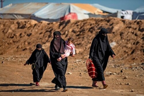 Women and accompanying children walk by at the Kurdish-run al-Hol camp for the displaced in the al-Hasakeh governorate in northeastern Syria on 14 January 2020, where families of Daesh foreign fighters are held. [DELIL SOULEIMAN/AFP via Getty Images]