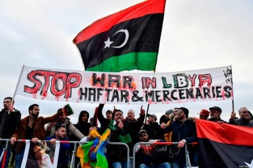 Protesters hold a banner reading 'Stop war in Libya, Haftar and mercenaries' during a protest in Berlin on 19 January 2020 [JOHN MACDOUGALL/AFP/Getty Images]