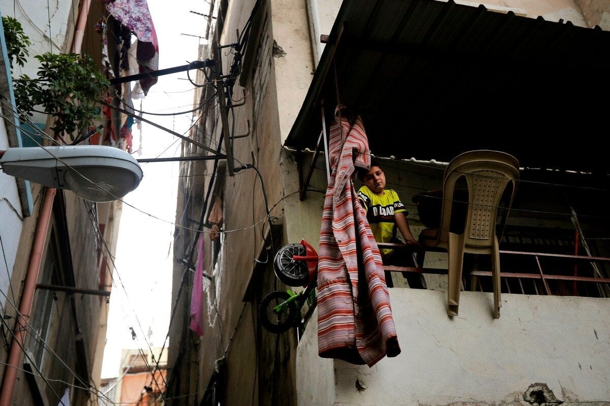 A boy looks out from a balcony in Tripoli, Lebanon 3 June 2020 [JOSEPH EID/AFP/Getty Images]