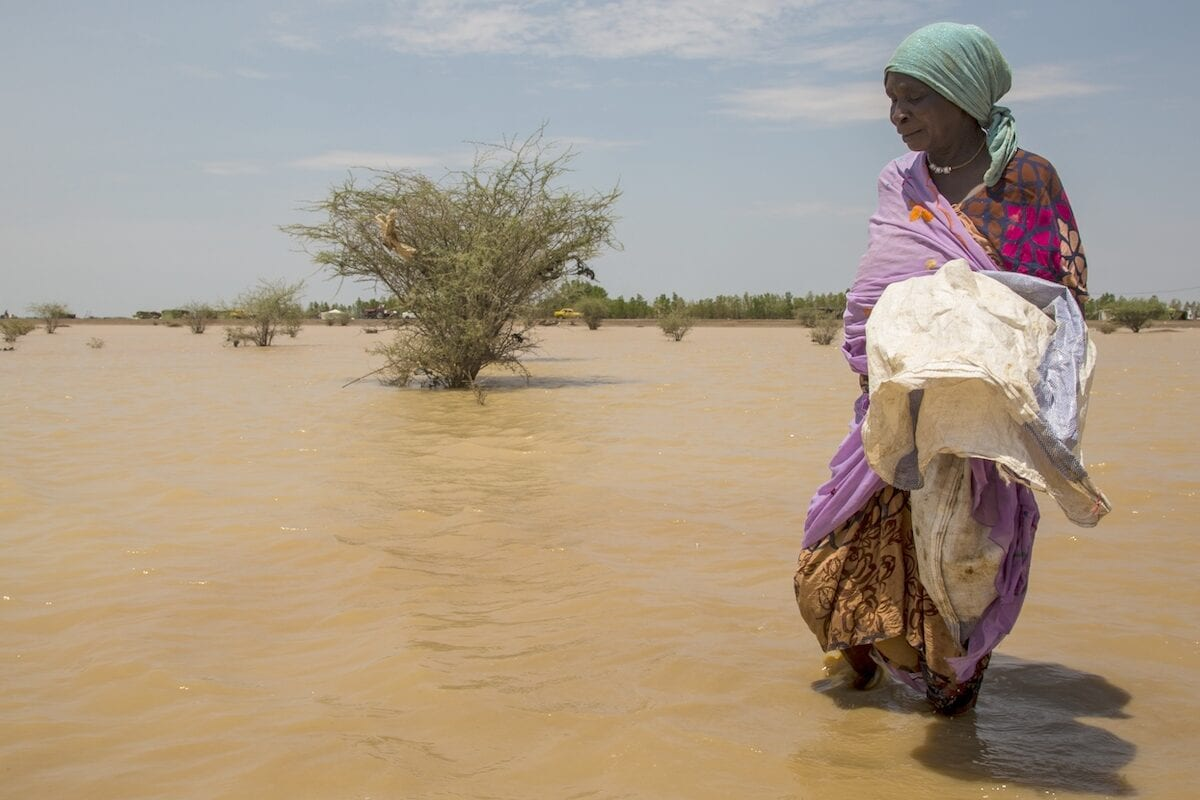 A woman is seen on a submerged area after floods on August 03, 2020 [Mahmoud Hjaj/Anadolu Agency]