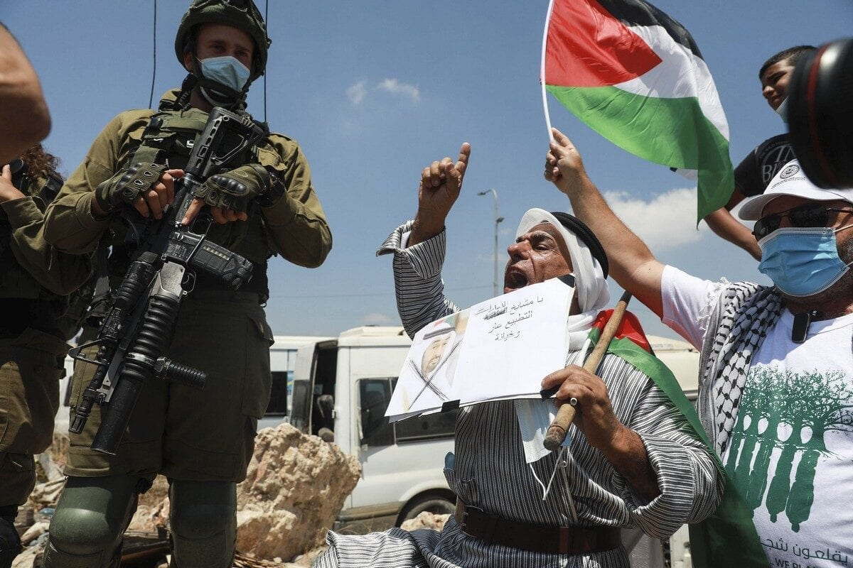 Palestinians gather to stage a protest against the agreement between UAE and Israel in the West Bank on 14 August 2020 [Issam Rimawi/Anadolu Agency]