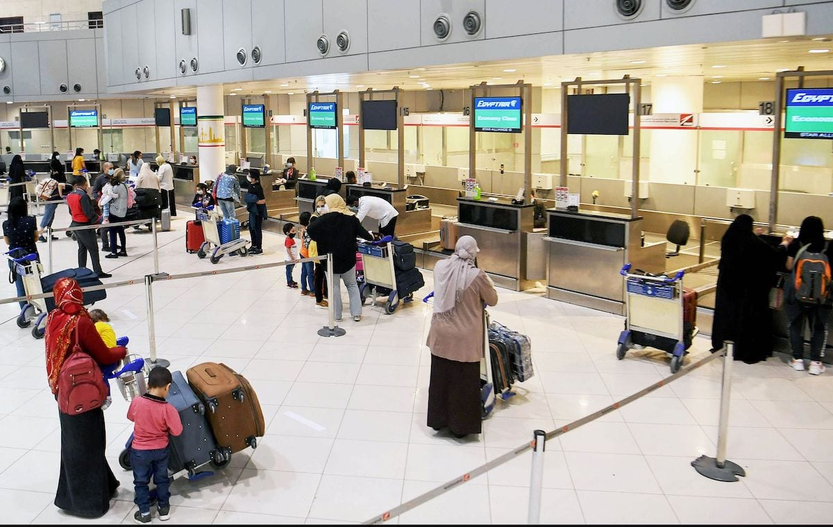 Egyptian citizens queue at Kuwait International Airport before boarding a repatriation flight to Cairo, in Kuwait City on 5 May 2020. [YASSER AL-ZAYYAT/AFP via Getty Images]