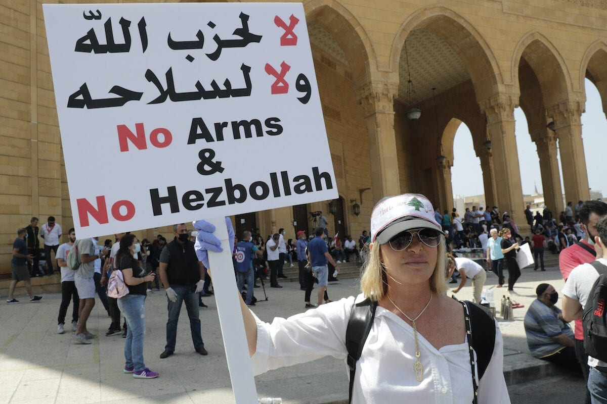 A Lebanese protester holds a placard in front of Mohammad al-Amin mosque during a demonstration in central Beirut, on 6 June 2020. [ANWAR AMRO/AFP via Getty Images]