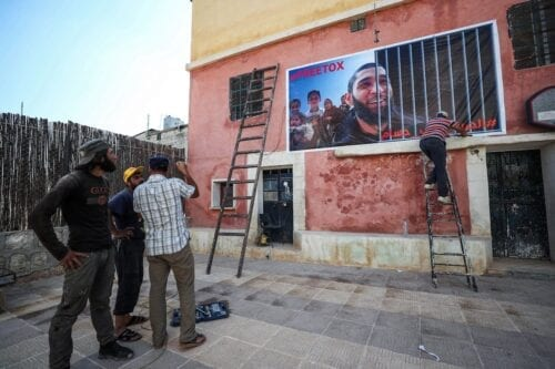 Men fix up a banner on the side of a building calling for the release of Tauqir Sharif, a self-described aid worker stripped of his British nationality and detained by Hayat Tahrir al-Sham (HTS) jihadists, at the premises of his charity organisation in the town of Atme in Syria's rebel-held northwestern Idlib province, on 1 July 2020. [OMAR HAJ KADOUR/AFP via Getty Images]