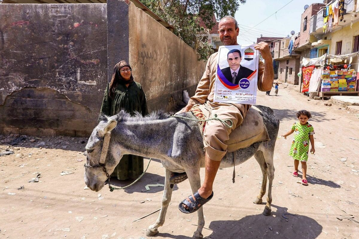 A man riding a donkey near a polling station in the town of el-Ayyat in Giza province south of the Egyptian capital on 11 August 2020 holds an electoral poster for a candidate running for the upper house election in the newly-created Senate. [AFP via Getty Images]