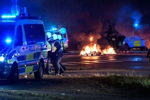 Riot police officers secure the area as smoke billows from burning tyres, pallets and fireworks as a few hundred protesters riot in the Rosengard neighbourhood of Malmo, Sweden, on 28 August 2020. [TT News Agency/AFP via Getty Images]