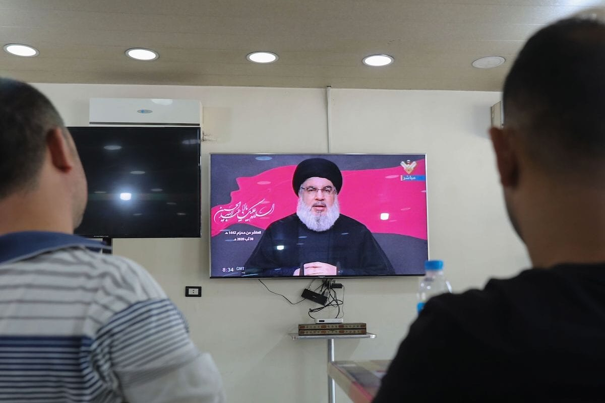 Lebanese men watch the head of the country's Shia Muslim movement Hezbollah Hassan Nasrallah during a televised speech, at a coffee shop in the southern suburbs of the capital Beirut, on 30 August 2020 [ANWAR AMRO/AFP via Getty Images]