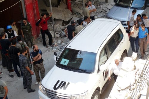 Syrians gather near a vehicle of the United Nations (UN) arms experts as they inspect a site suspected of being hit by a deadly chemical weapons attack last week on 28 August 2013 in the Eastern Ghouta area on the northeastern outskirts of Damascus. [MOHAMED ABDULLAH/AFP via Getty Images]