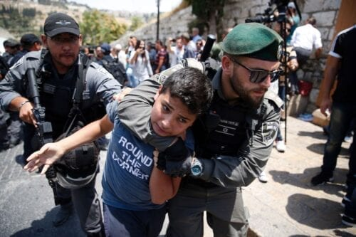 Israeli border guards detain a Palestinian child during a demonstration outside the Lions Gate, a main entrance to Al-Aqsa mosque compound, due to newly-implemented security measures by Israeli authorities which include metal detectors and cameras, in Jerusalem's Old City on 17 July 2017. [AHMAD GHARABLI/AFP via Getty Images]