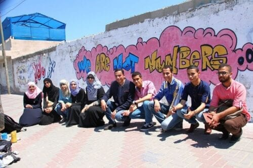 """Palestinian youth posing in front of a graffiti """"We Are Not Numbers"""" [Twitter]"""