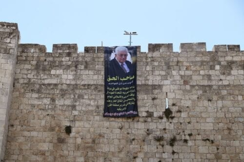 """Palestinian President Mahmoud Abbas is depicted on a banner hung on the walls of Jerusalem's Old City August 20, 2020. The writing in Arabic reads, """"The rightful owner Is stronger than all the capitals. We call upon the government of Abu Dhabi in the United Arab Emirates to revert to the inclusive Arab and Islamic position and to withdraw from the shameful agreement, and not to participate in making the American Deal of the Century pass. Jerusalem's wounds are not to be treated with the salt from your capitals."""" [Ammar Awad/Twitter]"""