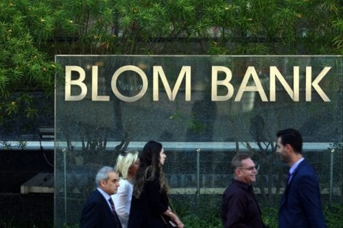People walk past BLOM BANK in the Lebanese capital Beirut on 13 June 2016 [PATRICK BAZ/AFP/Getty Images]