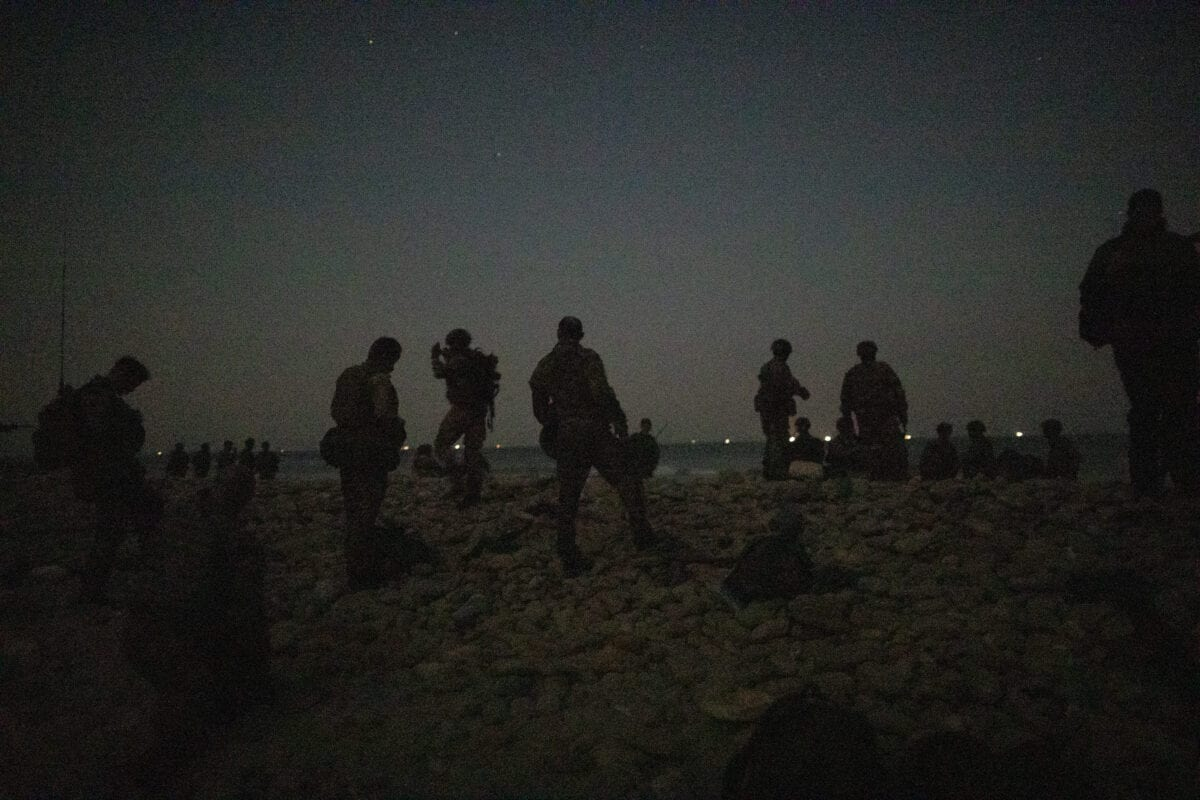 DUQM, OMAN - OCTOBER 24: Personnel from 40 Commando, Royal Marines arrive on a beach at night after moving from RFA Lyme Bay for a night time amphibious raid during exercise 'Saif Sareea 3' on October 24, 2018 in the Arabian Sea, Oman. [Dan Kitwood/Getty Images]