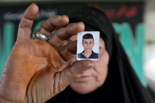 An Iraqi woman holds a photo of her son, whom she said she lost contact with more than a week ago, during an anti-government protest on Baghdad's Siniq Bridge in the heart of the Iraqi capital on 24 November 2019. [SABAH ARAR/AFP via Getty Images]