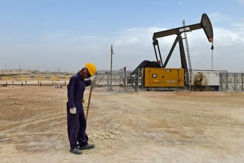 A worker stands across a pumpjack operating in the desert oil fields on April 22, 2020 [MAZEN MAHDI/AFP via Getty Images]