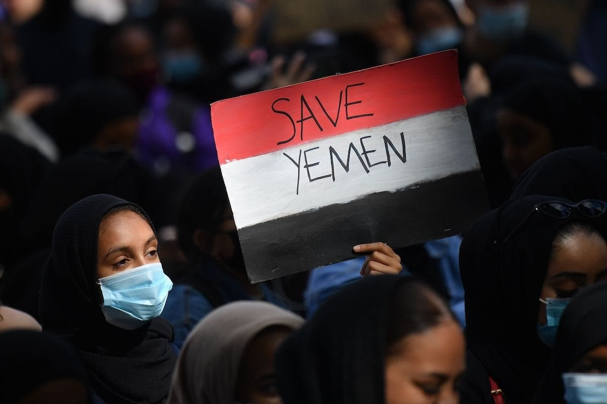 A protester holds a Yemeni flag-themed placard in Parliament Square in London on 5 July 2020, as she demonstrates against the continued conflict in Yemen. [JUSTIN TALLIS/AFP via Getty Images]
