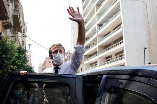 French President Emmanuel Macron waves from his vehicle during a visit in Beirut, Lebanon, on 6 August 2020 a day after a massive explosion devastated the Lebanese capital in a disaster that has sparked grief and fury. [THIBAULT CAMUS/POOL/AFP via Getty Images]