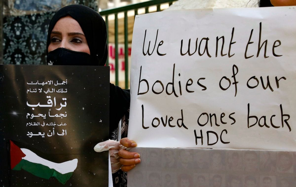 Palestinians hold placards during a demonstration to demand the return of the bodies of relatives who were allegedly involved in attacks and consequently killed by Israeli forces, in the West Bank town of Hebron, on 30 August 2020. [HAZEM BADER/AFP via Getty Images]