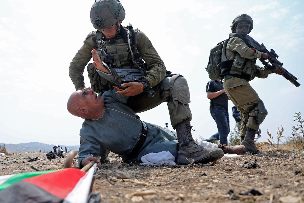 An Israeli soldier detains a Palestinian man in the West Bank, on 1 September 2020 [JAAFAR ASHTIYEH/AFP/Getty Images]