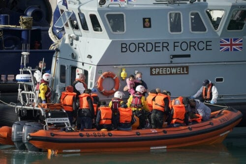 A young girl is held by a member of the border force at Dover Marina after being rescued in the English Channel by the RNLI on 7 September 2020 in Dover, England. [Christopher Furlong/Getty Images]
