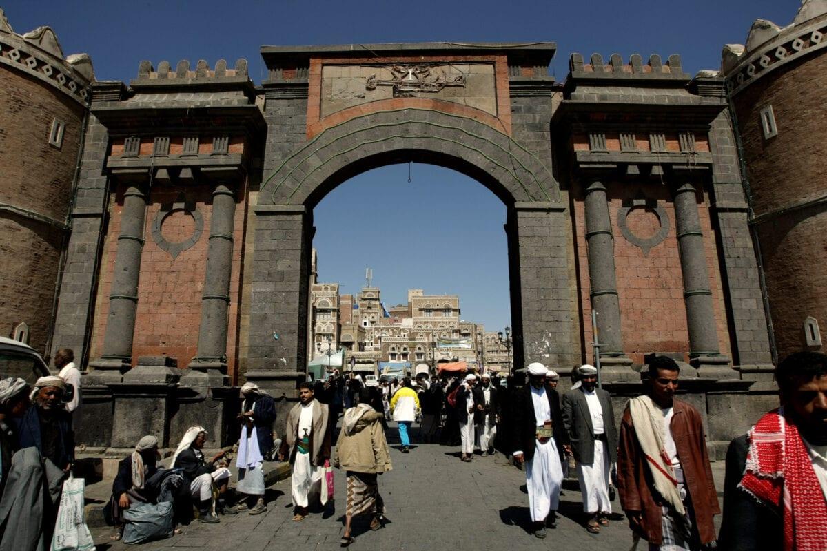 Yemenis walk under the iconic Yemen Gate leading to the old city of Sanaa on November 8, 2009 [MARWAN NAAMANI/AFP via Getty Images]