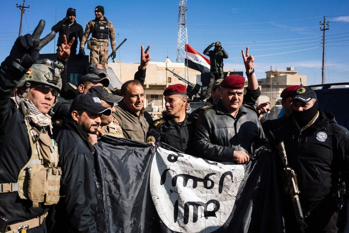 Members of the Iraqi special forces Counter Terrorism Service (CTS) hold an Islamic State (IS) group flag as they celebrate in their military base in the town of Bartalla on January 18, 2017 after a top Iraqi commander announced that have they fully retaken east Mosul from the Daesh [DIMITAR DILKOFF/AFP via Getty Images]