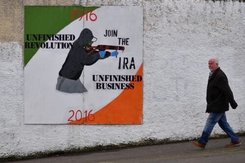 A man walks past a Republican mural in the Bogside area of Derry on March 22, 2017. [BEN STANSALL/AFP via Getty Images]