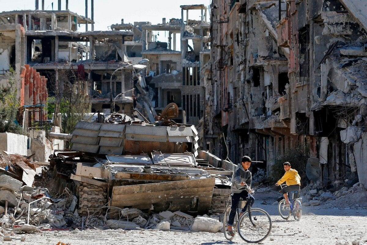 Boys ride their bicycles in a street near destroyed buildings in the Palestinian camp of Yarmuk in Damascus, Syria on 1 November 2018 [LOUAI BESHARA/AFP/Getty Images]